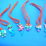 wholesale amber necklaces. Hawaiian sunset colored wooden pendant charms on multi string necklace.