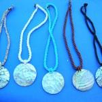 wholesale imitation amber necklaces. Large circle seashell fashion pendant on single beaded string necklace.