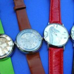 watch wholesaler. Fun theme clock face design on ladies watch, with colored imitation leather band.