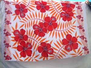 red hibiscus flower red palm leaf Indonesian sarong on white background
