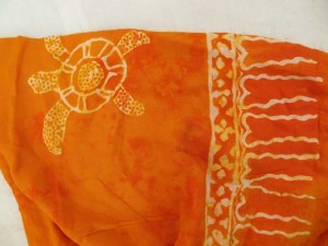 monocolor orange sarong screen printings with leaves, sun, dolphin, seashell, palm leaves etc tropical designs