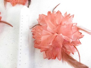 Light orange red color flower corsage with glitter edging and feather
