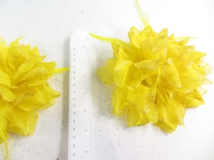 Yellow color flower corsage with glitter edging and feather