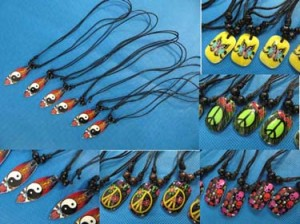 Painted resin pendant necklace with adjust black cord. Mixed designs of gothic skull, peace sign, butterfly and yingyang