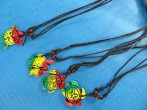 Reggae rasta resin pendant necklace hippy Rastafarian Jamaican style jewelry Adjustable black cord. Mixed designs include peace sign, swirl, kokopelli, sun face, turtles