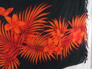 orange plumier flower leaf on black sarong